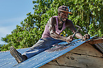 Deravil Samile roofs a new house in Picmy, a village on the Haitian island of La Gonave, one of many houses built by Service Chrétien d'Haïti for survivors of the 2016 Hurricane Matthew. SCH is a member of the ACT Alliance.