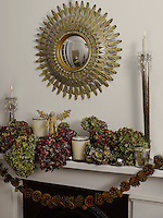 An ornate metal convex mirror hangs over the mantelpiece decorated for Christmas with dried hydrangeas and pine cones