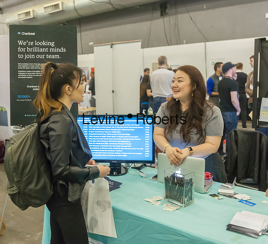 Workers from Chartbeat speak to attendees at the TechDay New York event on Tuesday, April 18, 2017. Thousands attended to seek jobs with the startups and to network with their peers. TechDay bills itself as the U.S.'s largest startup event with over 500 exhibitors. (© Richard B. Levine)