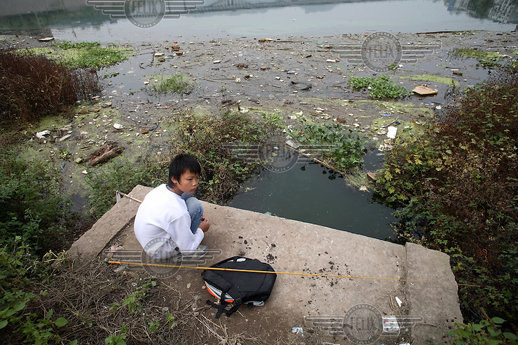"""A young boy fishes in the polluted waters of the """"Heavenly Immortal Lake"""", which opens up into the Yangtze River."""