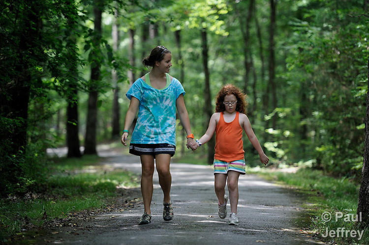 Counselor Madison Nix walks with camper Jalei Mannis along a path through the quiet woods at Camp Aldersgate in Little Rock, Arkansas. The camp, supported by United Methodist Women, offers children suffering from a variety of disabilities a safe and fun experience similar to that which normally-abled children often enjoy.