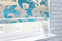 The vibrant blue colour of the birds and insects on this blind bring a cheerful dash of colour to the white tiles of this bathroom