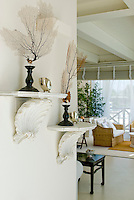 Sea inspired coral and shells are displayed on white shelves in this bright living room