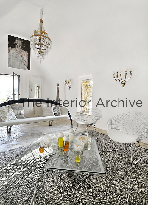 The living room is furnished with a sofa by Andrea Branzi and a collection of Bertoia chairs grouped around a glass-topped coffee table