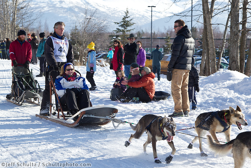 Linwood Fiedler and team run past spectators on the bike/ski trail during the Anchorage ceremonial start during the 2013 Iditarod race.    Photo by Britt Coon/IditarodPhotos.com