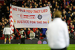 Manager of Liverpool, Jurgen Klopp looks on towards a banner protesting about the Sun newspaper during the UEFA Europa League match at Anfield. Photo credit should read: Philip Oldham/Sportimage