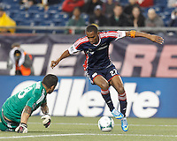 New England Revolution forward Jerry Bengtson (27) works to elude Real Salt Lake goalkeeper Nick Rimando (18). In a Major League Soccer (MLS) match, Real Salt Lake (white)defeated the New England Revolution (blue), 2-1, at Gillette Stadium on May 8, 2013.
