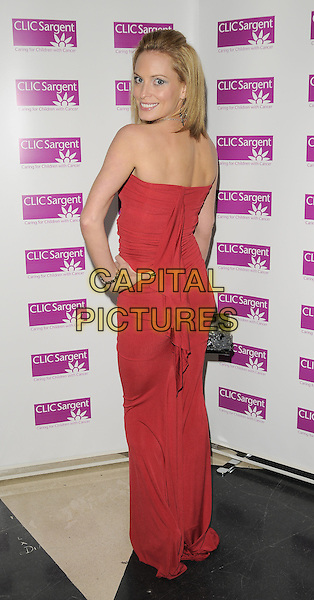 JOANNA TAYLOR.The Ruby Ball, The Brewery, Chiswell St., London, England..November 21st, 2008.full length red strapless dress black bag purse long hand on hip looking over shoulder .CAP/CAN.©Can Nguyen/Capital Pictures.