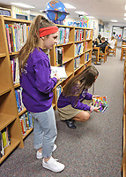 Maggie Gollnick and Megan Cunningham help out in the library at Our Lady of Grace School in Noblesville.