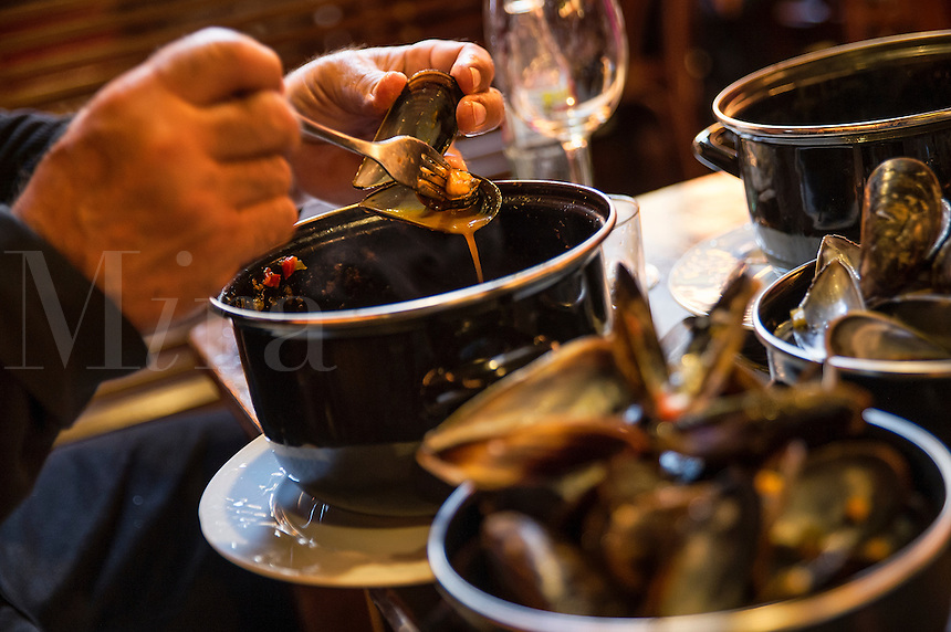 Patron enjoys a mussel dish at a tapas restaurant, Barcelona, Spain
