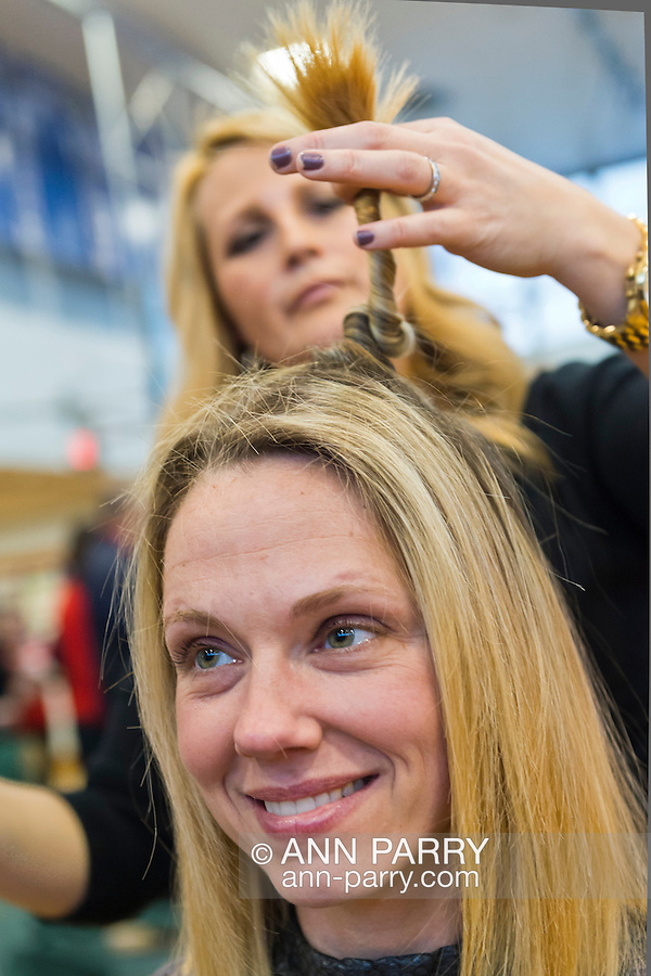 WENDY SIMSON, a Calhoun High School teacher, is having haircut by BRENDA GALLO, a graduate of Calhoun, at St. Baldrick's fund raising event at the school. Simson is participating to honor her cousins who died of melanoma and cervical cancer. The Long Island school  exceeded its goal of raising $50,000 for childhood cancer research. Plus, many ponytails cut off will be donated to Locks of Love foundation, which collects hair donations to make wigs for children who lost their hair due to medical reasons.