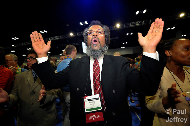 Frederick Brewington, a delegate from the New York annual conference, was among dozens of demonstrators demanding a more inclusive church who took over the floor of a May 3 session of the 2012 United Methodist General Conference in Tampa, Florida. They held communion around the center table and sang songs. Several remained around the table, causing the presiding bishop to suspend the morning session.