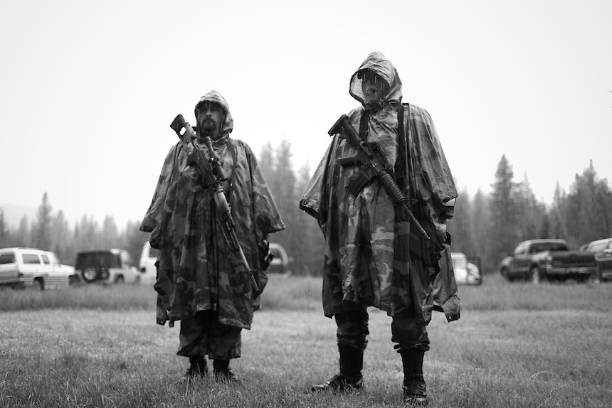 Jeff Stankiewicz, Commander of the Idaho Light Foot Militia, stands in the rain with Captain Willard Protsman during a weekend long training session on public lands near Priest Lake, Idaho.