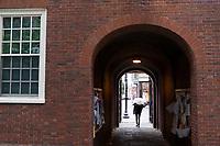 People walk through a gate opening onto Massachusetts Avenue through Wigglesworth Hall, one of Harvard's freshman dorms, at Harvard University in Cambridge, Massachusetts, USA, on Mon., Oct 15, 2018.