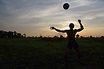 A man plays volleyball at sunset in the village of Dong in northern Cambodia.