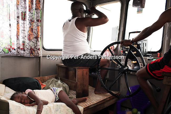 MBANDAKA, DEMOCRATIC REPUBLIC OF CONGO JUNE 25: Captain Pascal Thomolo, age 65, scans the river in his binoculars as his daughter, Mama Thomolo, age 5, is sleeping on a bed next to him while traveling on the Congo River on June 25, 2006 outside Mbandaka, Congo, DRC. Captain Thomolo has worked on the river for 23 years and is soon to retire after a long career without any accidents. He has been married several times and has twenty children. His boat traveled with about 150 passengers from Bumba to Kinshasa, a journey of about 1300 kilometers. The Congo River is a lifeline for millions of people, who depend on it for transport and trade. Passengers slept in the open, with their goats, pigs and other animals. Boat travel is the only option for most people along the river as there?s no roads or infrastructure. Very few can afford to fly in a plane to the capital Kinshasa. During the Mobuto era, big boats run by the state company ONATRA dominated the river. These boats had cabins and restaurants etc. All the boats are now private and are mainly barges that transport goods. The crews sell tickets to passengers who travel in very bad conditions. The conditions on the boats often resemble conditions in a refugee camp. Congo is planning to hold general elections by July 2006, the first democratic elections in forty years. The Congolese and the international community are hoping that Congo will finally have piece and the country will be rebuilt..(Photo by Per-Anders Pettersson).