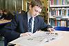 Secondary school student reading a newspaper in the school library,