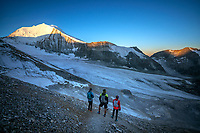 Three runners watching the sunrise on the Bishorn while on the Via Valais, a multi-day trail running tour connecting Verbier with Zermatt, Switzerland.
