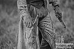 A fine art black and white photograph of a cattle rancher waiting to vaccinate calves during a branding. Cowboy Photos, riding,roping,horseback
