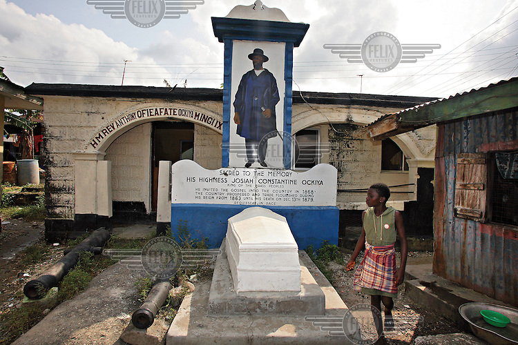 A girl walks past the tomb of King Josiah Constantine Ockiya, Mingi VII.