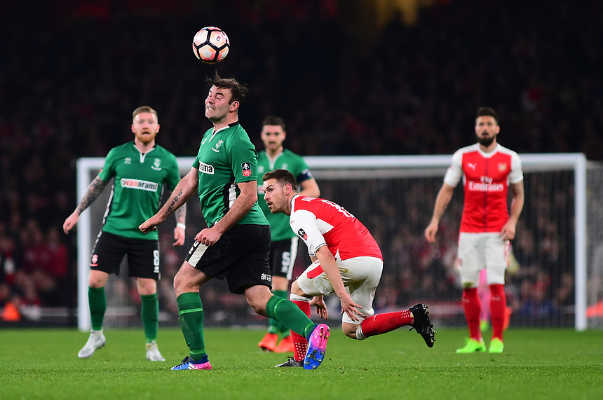 Lincoln City's Matt Rhead heads forward under pressure from Arsenal's Aaron Ramsey<br /> <br /> Photographer Andrew Vaughan/CameraSport<br /> <br /> The Emirates FA Cup Quarter-Final - Arsenal v Lincoln City - Saturday 11th March 2017 - The Emirates - London<br />  <br /> World Copyright &copy; 2017 CameraSport. All rights reserved. 43 Linden Ave. Countesthorpe. Leicester. England. LE8 5PG - Tel: +44 (0) 116 277 4147 - admin@camerasport.com - www.camerasport.com
