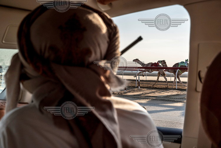 Racing camel owners follow the animals in their SUVs. A radio receiver is placed in the front pocket of the robot jockey and the owner shouts commands to the machine as the race progresses.