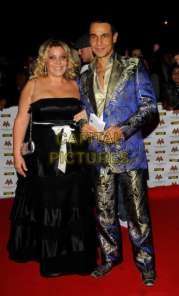 GUEST & CHICO SLIMANI.MOBO Awards at Wembley Arena, London, England. .October 15th, 2008 .MOBOS music of black origin full length black strapless dress gown blue gold suit pattern white bow ribbon .CAP/CAN.©Can Nguyen/Capital Pictures.