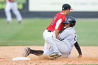 Osvaldo Martinez #2 of the Jacksonville Suns collides with Jake Kahaulelio #3 of the Carolina Mudcats as he steals second base at Five County Stadium May 16, 2010, in Zebulon, North Carolina.  Photo by Brian Westerholt /  Seam Images
