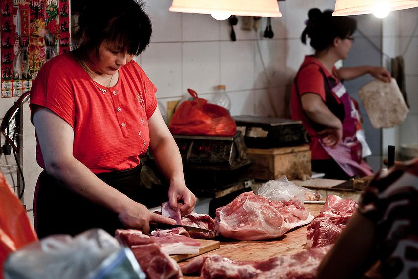 Pork meat seller in a wet market of Beijing. 2011