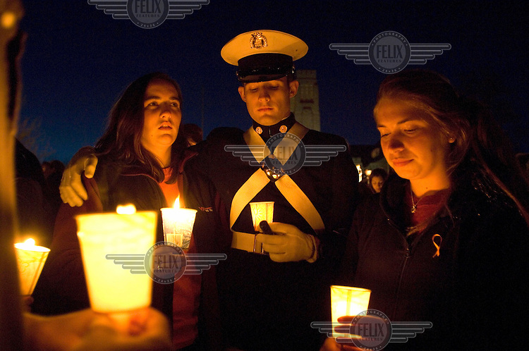 Mourners Brianna Arthurs, Steven McArthur (a Virginia Tech cadet) and Emily Kirschner, left to right, grieve at a candlelit vigil for the victims of the shooting massacre at Virginia Tech University the previous day. 33 people died in what was the deadliest school shooting in US history.