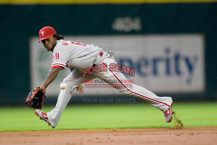 Philadelphia Phillies shortstop Michael Martinez #19 fields a ground ball during the Major League Baseball game against the Houston Astros at Minute Maid Park in Houston, Texas on September 14, 2011. Philadelphia defeated Houston 1-0 to clinch a playoff berth.  (Andrew Woolley/Four Seam Images)