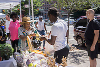 Shoppers purchase bread from the Hot Bread Kitchen at the Fortune Society's Fortune Fresh farm stand at the Grassroots Farmers Market in Harlem in New York on Saturday, August 24, 2013. The Fortune Society develops programs, including Culinary Skills/Food Service Training, for former prisoners and young people involved in the criminal justice system preventing recidivism. (© Richard B. Levine)