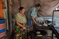 Bangladesh, Jhenaidah. Kalpana (woman) cooking in their little roadside restaurant with her husband. They make chapati and lentils and she earns about 15 TK  US$18 per month. She burned her arm when she cooking and the dress material stuck to her arm, they have four grown children. Model released.
