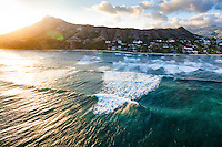 At sunset, waves roll in towards Diamond Head Beach on O'ahu.