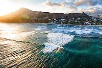 At sunset, waves roll in towards Diamond Head Beach on O'ahu.