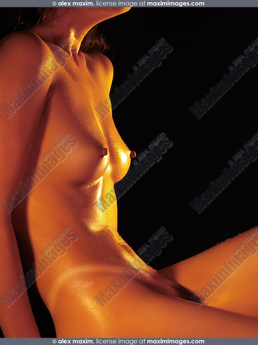 Beautiful naked suntanned shiny woman's body on black background