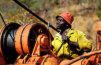 Southern Africa.  Mineral exploration driller working a winch during exploration in the bush..