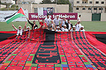 Palestinians display the largest traditional Palestinian dress it will be to create the largest traditional Palestinian dress in an attempt to enter the Guinness World Records at Al-Hussein stadium in the West Bank city of Hebron on October 25, 2009. the largest traditional Palestinian dress include knitted olive tress, Falastin (Palestinian), Palestinian flag and the word 'Al-Quds' (Jerusalem) Photo by Najeh Hashlamoun