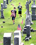 WINSTED CT. 18 May 2018-051818SV07- From left, Caleb Goodell and Mason Goodell both 14, of Winsted help their family replace old American Flags with new ones at a cemetery on Oak Street in Winsted Friday. The family replaces the flags at that cemetery every year before Memorial Day.<br /> Steven Valenti Republican-American