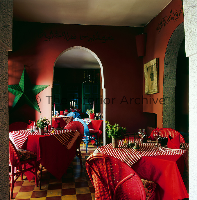 The dining room has a warm, intimate feel with deep orange walls and red table linen.