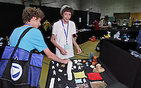 "OrigamiUSA 2014 exhibition. The Zimet brothers, Nathan and  Avi, look over Malachi Brown's ""Please Touch"" origami exhibit. The exhibit tables are all marked ""Please Do Not Touch"" with the exception of Malachi's exhibit."
