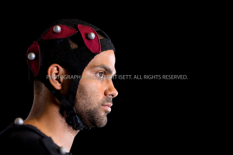 7/29/2008--Vancouver, BC, Canada..Tony Parker, NBA LIVE 09 Cover Athlete (San Antonio Spurs)  puts on a custom fit motion capture suit and has  reflective balls attached at EA (Electronic Arts) World Wide Motion Capture Facility in Vancouver, British Columbia, Canada. EA is an American developer, marketer, publisher, and distributor of computer and video games...The NBA players wear custom fit motion capture suit and have reflective balls, called ?markers? (not sensors), attached to the suit with Velcro. The markers are made of rubber and are covered with reflective tape...Each camera has its own light source, the red ring around each camera ? the lens is the dark spot in the centre. The red light shines into the shoot area, hits the marker and reflects the light back to the camera. The camera records that point of light as a dot on the screen. The software identifies each dot and mocap staff take those dots and attach them to the character provided by the game team. The ?bones? of the game character are pulled around by the dots in the same manner a string would pull a marionette?s body around...A typical team will shoot 8-10 days of motion capture each year and capture about 20,000 seconds (5.5 hours) of animation. The animators on the game team can then manipulate the data as they see fit and deliver it to the software engineers to put into the game...©2008 Stuart Isett. All rights reserved.