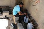 A Palestinian youth fills bottles with water from a spring water in the village of Iraq Burin, in the West Bank city of Nablus on July 1, 2010 as Palestinians in the village suffer from the shortage of water. Israel on Thursday morning, increased the price of water 5%. Photo by Wagdi Eshtayah