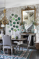 A collection of green ceramic 'leaf' plates is a whimsical feature on the Ralph Lauren floral wallpaper of the dining room