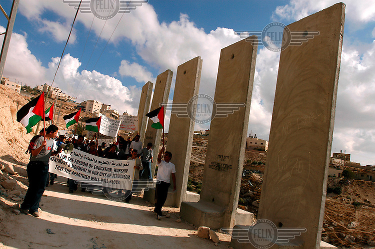 Palestinians demonstrate against the separation wall Israel is building, marching near concrete barricades at the West Bank village of Sawachre..