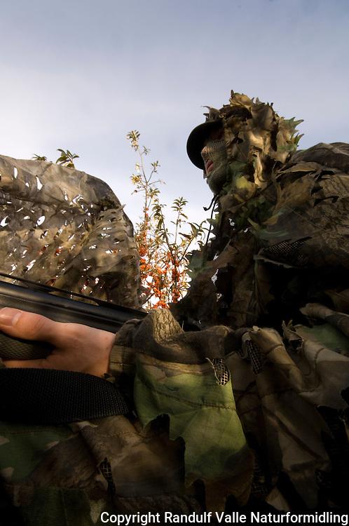 Mann med hagle bak kamuflasjenett ---- Man with shotgun behind camouflage net