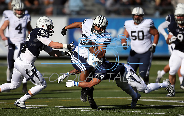 BYU running back Paul Lasike (33) runs against Nevada defenders Alex Bertrando (56), left, and Matthew Lyons (9) during an NCAA college football game in Reno, Nev., on Saturday, Nov. 30, 2013. (AP Photo/Cathleen Allison)