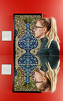 BNPS.co.uk (01202 558833)<br /> Pic: ZcharyCulpin/BNPS<br /> <br /> Pictured: Emma Rowland from the Russell-Coates Art Gallery with a Flowers in a Vase tile panel. This panel was based on an Islamic design that De Morgan saw at the South Kensington Museum (now the V&A). The panel is reflected in a mirror.<br /> <br /> 'Sublime Symmetry' at the Russell-Coates Art Gallery and Museum in Bournemouth, Dorset<br /> <br /> The Sublime Symmetry exhibition showcases the work of William De Morgan. The celebrated Arts and Crafts designer (1939-1917) was seen as the most inventive ceramic designer of the Victorian period.  The exhibition which runs until the 2nd February explores the Mathematics behind De Morgan's Ceramic designs.