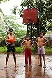 PHILIPPINES, Palawan, Puerto Princesa, Ian, Marvin and Nestor play basketball on Abanico Road in Barangay Village, San Pedro