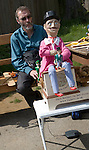 Man operating a traditional wooden jig doll dancer during a country folk event at Shottisham, Suffolk, England